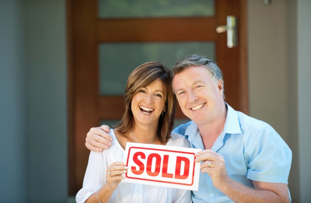 Longview Melbourne real estate a couple holding sold sign